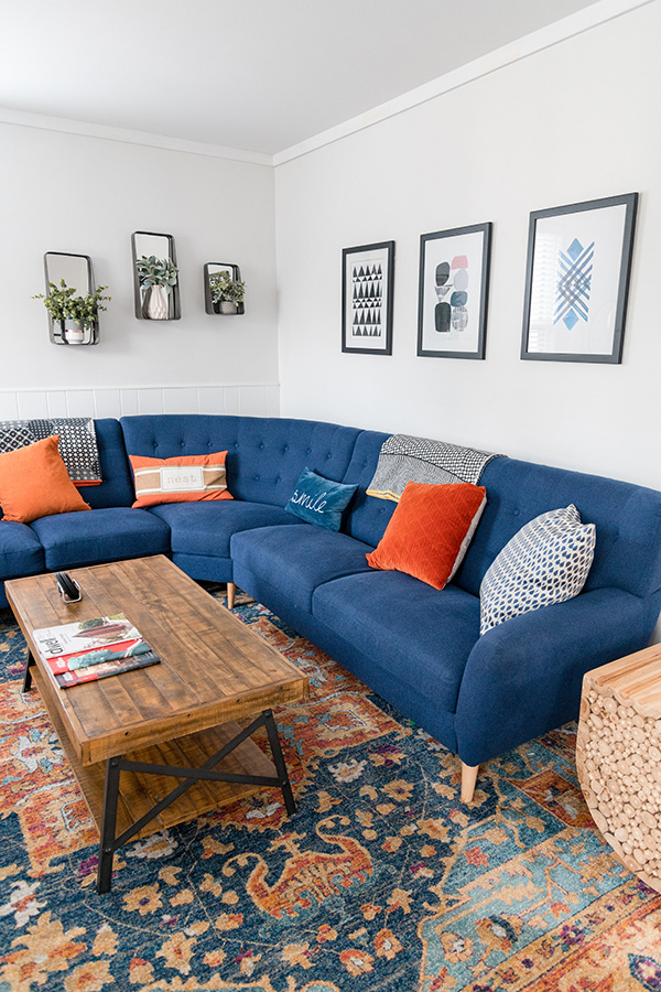 Apartment living room with bright white walls, plush blue sectional with decorative pillows, and large patterned rug.