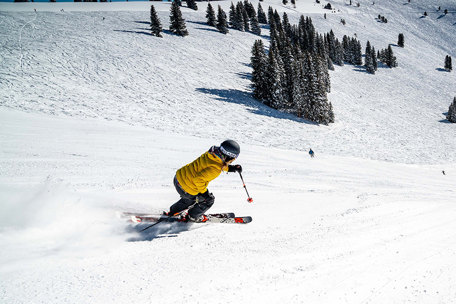 Person in yellow jacket skiing down steep mountain run lined with dark pine trees.