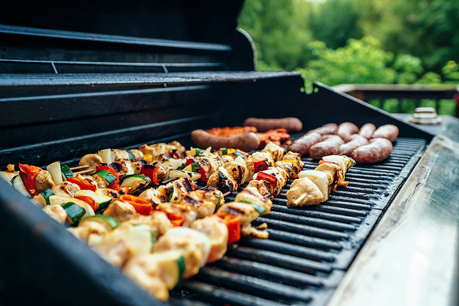 Wide stainless steel BBQ grill with charred kebabs and sausages.