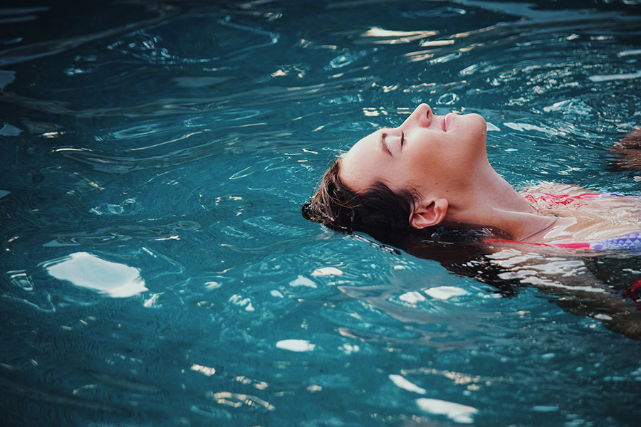 Relaxed person in bikini floats on their back in a deep blue pool.