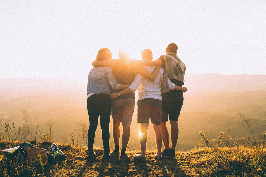 Group of four people on mountain top embrace and face the warm afternoon sun.