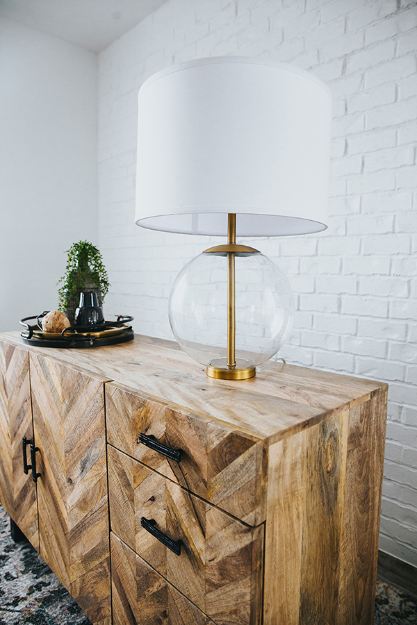 Geometric pattern wood console topped with brass lamp with glass globe and white shade in front of white painted brick wall.