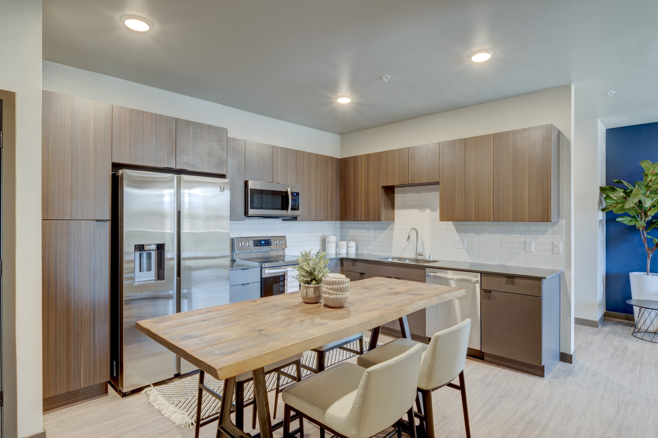 Kitchen with wood floor and cabinets, stainless steel appliances and tall live edge wood dining table with stools.
