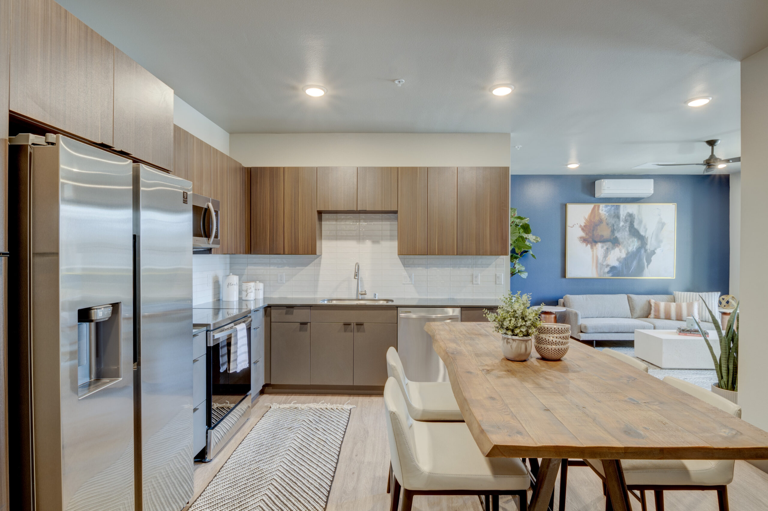 Kitchen and dining space with wood floor and cabinets, stainless steel appliances and large live edge wood table with chairs.