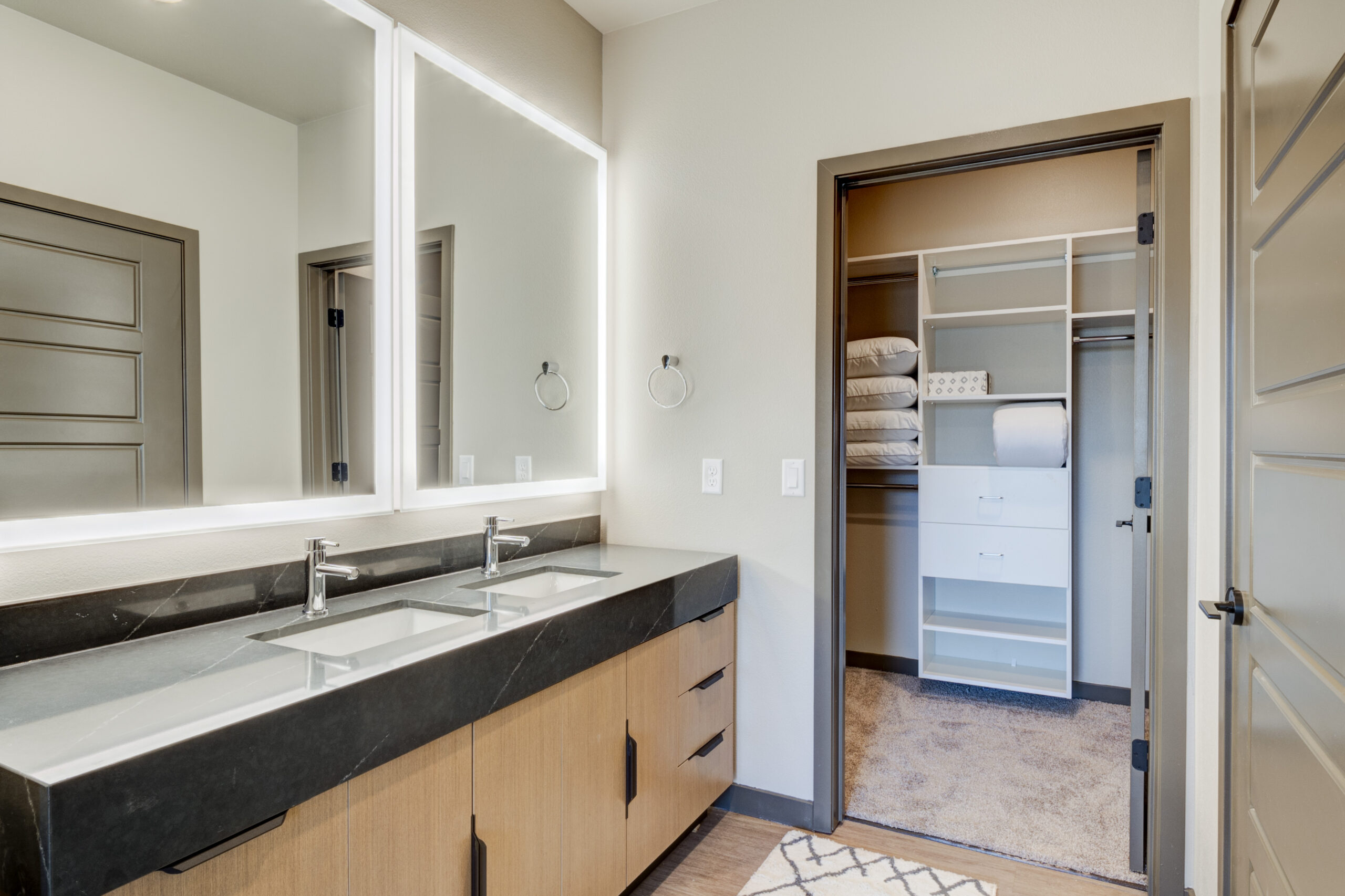 Bathroom with wood floor and cabinets, stone counter, dual lighted mirrors, and door to walk in closet.